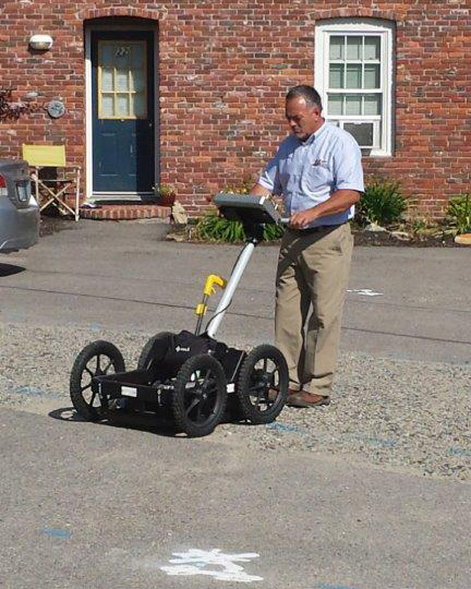 Glen locating a water pipe in a parking lot using ground penetrating radar