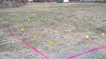 A painted and flagged outline of a buried Undeground Storage Tank (UST) found with ground-penetrating radar.